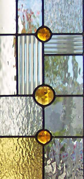 Closeup of custom abstract stained and leaded glass sidelight window inspired by frank lloyd wright