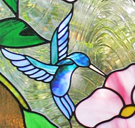 Closeup of custom stained and leaded glass hummingbird and flowers window