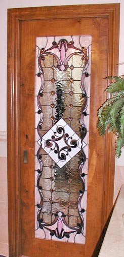 Victorian style stained and leaded glass custom door window separating a walk-in closet and bathroom